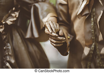 Bronze painted couple. Focus on his hands - Man and...
