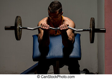 fitness trainer doing heavy weight exercise for biceps