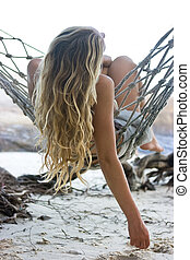 Woman in hammock - Blond girl lying in hammock on the beach
