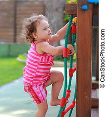 Small girl child climbing up on children activity ladder...