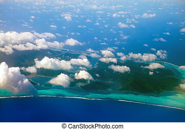 Polynesia. The atoll in ocean through clouds. Aerial view