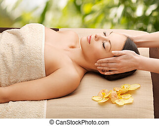 woman in spa getting facial massage - spa and holidays -...