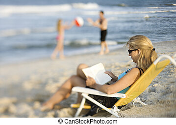 Mom reading book on beach. - Caucasian mother reading in...
