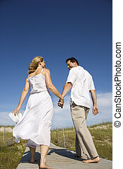 Couple holding hands walking down path.
