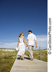 Couple holding hands walking down path - Caucasian mid-adult...