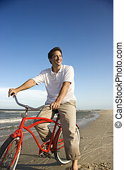 Man riding red bicycle on beach.