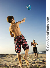 Boy throwing football with dad. - Caucasian pre-teen boy...