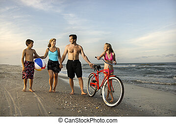 Family walking down the beach. - Caucasian family of four...