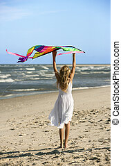 Girl holding kite on beach. - Caucasian pre-teen girl...
