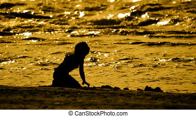 Silhouette of a little girl on the beach