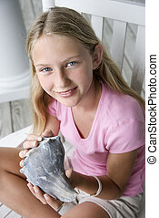 Girl holding conch shell - Caucasian pre-teen girl sitting...