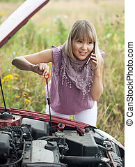 woman trying to fix the car - Young woman trying to fix the...