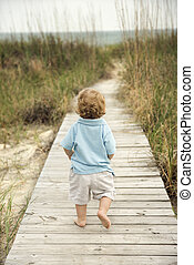 Little boy on beach walkway - Caucasian male toddler walking...