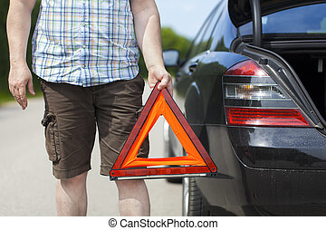 Man with warning triangle near car on the road