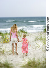 Sisters walking on beach - Caucasian pre-teen girl holding...