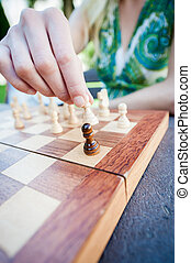 Woman moves piece in chess