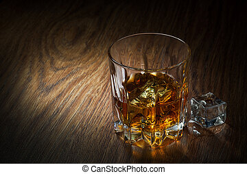 Whiskey with ice in glass on the wood