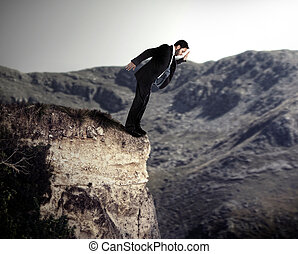 Young businessman falls from the cliff.