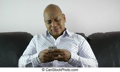 african american businessman using smart phone emailing at...