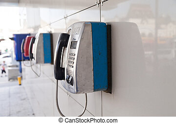 Payphones on a wall waiting for calls and people