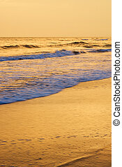Waves lapping on beach at sunset