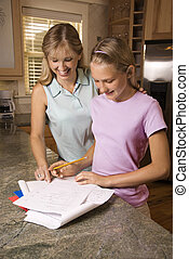 Mom helping daughter with homework.