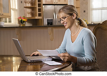 Woman on computer. - Caucasian mid-adult woman paying bills...