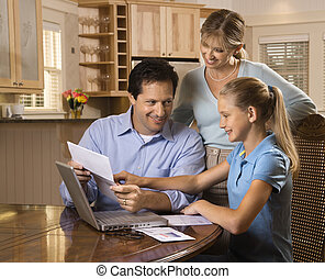 Family on computer - Caucasian family paying bills on laptop...