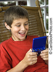 Boy playing video game. - Caucasian pre-teen boy playing...