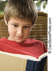 Boy reading book. - Caucasian pre-teen boy reading book.