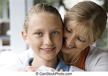 Mom hugging daughter.