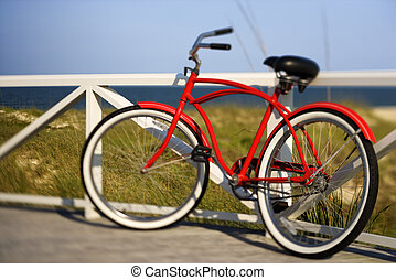 Bicycle at beach. - Red beach cruiser bicycle leaning...