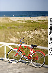 Red beach cruiser bicycle. - Bicycle leaning against rail on...