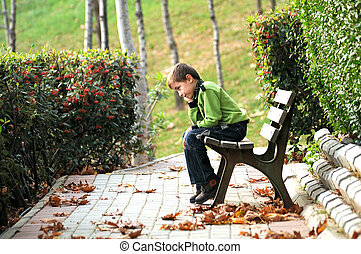 sad boy sitting alone on a bench in a way - sad lonely child...