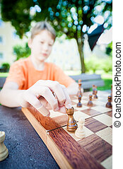 Boy moves piece in chess