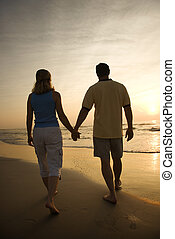 Couple on beach at sunset - Caucasian mid-adult couple...