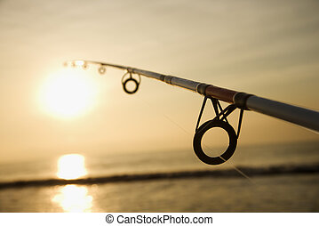 Fishing pole at sunset - Fishing pole against ocean at...