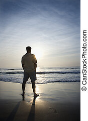 Man alone on beach. - Caucasian mid-adult man standing alone...