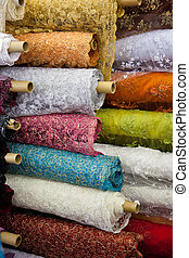 Bolts/rolls of various colored fabric - A background of...