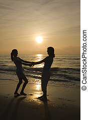 Mom and daughter on beach - Caucasian mid-adult mother and...