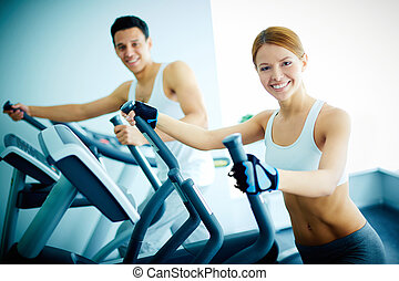 Training in health club - Portrait of pretty girl and young...