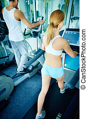 Training on sport facilities - Rear view of girl and guy...
