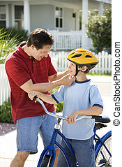 Dad helping son with helmet - Caucasian mid-adult dad...