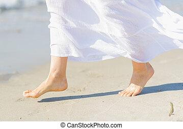 Closeup on leg of young woman on sea coast