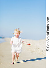 Happy baby running on beach
