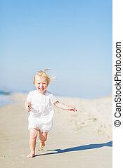 Happy baby running on beach