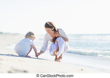 Mother and baby playing on beach