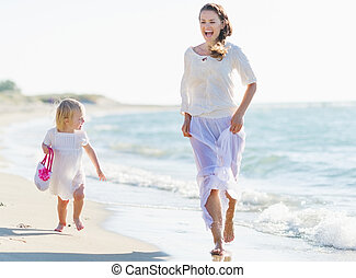 Happy mother and baby running on sea shore