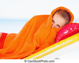 Young woman wrapped in towel laying on chaise-lounge
