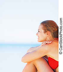 Happy young woman sitting on beach and looking on copy space